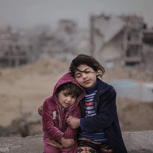 Una niña palestina protege a su hermana del frio.